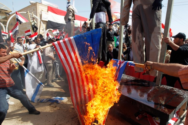 Supporters of Shi'ite cleric Moqtada al-Sadr burn a U.S. flag during demonstration in Najaf April 9, 2010. Anti-U.S. cleric Moqtada al-Sadr, a key player in forming a new Iraq government, urged Sunni and Shi'ite Muslims on Friday to unite to oust American troops. REUTERS/Thaier Al-Sudani (IRAQ - Tags: POLITICS CIVIL UNREST RELIGION)